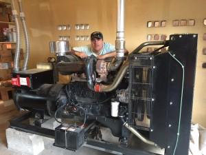 Steve Marcer standing with generator in Haiti
